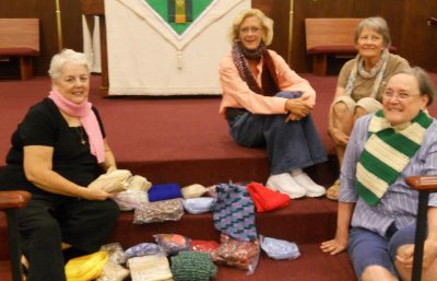 Women in the prayer shawl ministry with the scarves they knitted and crocheted
