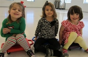 Three small girls seated on the floor and smiling for the camera