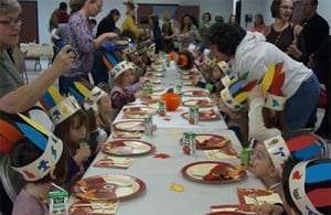 Long table of children wearing paper hats witha adults helping them at a Thanksgiving meal