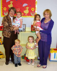 Two older women pictured with four young children in the child care room