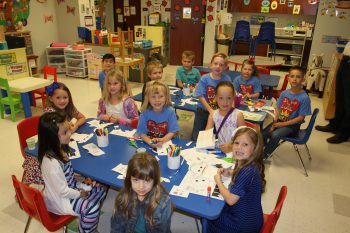 Children seated around small tables coloring with crayons in Sunday school