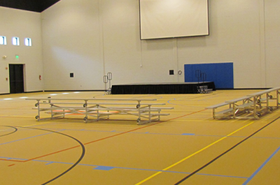 Empty Messiah gymnasium with empty bleacher seats in front of blank projector screen