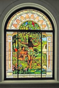 Stained glass window portrait of Adam and Eve in the garden with animals.