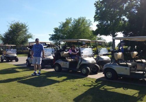 Group of golf carts with three men nearby
