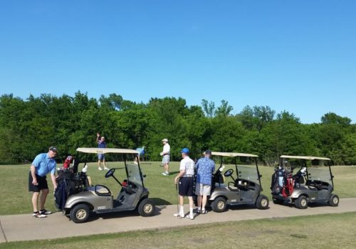 Golfers at the green standing near their golf carts