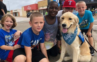 Triton the comfortdog posing for a phot with a group of young children