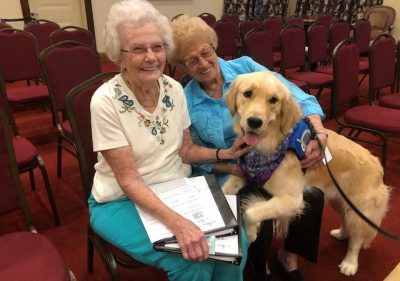 Triton the comfortdog sitting with two women in seating aisles