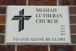 "Plaque engraved ""Messiah Lutheran Church 1957, 1975, 2003, 2012. To God Alone be Glory"" with a cross"