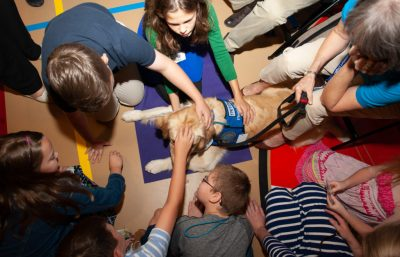 Triton the comfortdog being petted by a group of young children