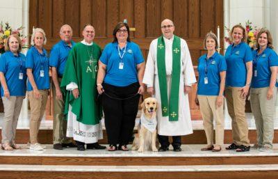 Triton the comfortdog posing with Messiah Lutheran staff and pastors