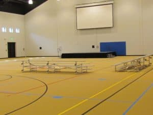 Empty gymnasium with some seating and a pull down projector screen above a platfrom.