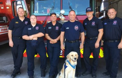 Triton the comfortdog sitting with Fire Department crew in front of their fire truck parked in garage