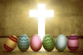 Painted Easter eggs lined up in front of a bright shining cross