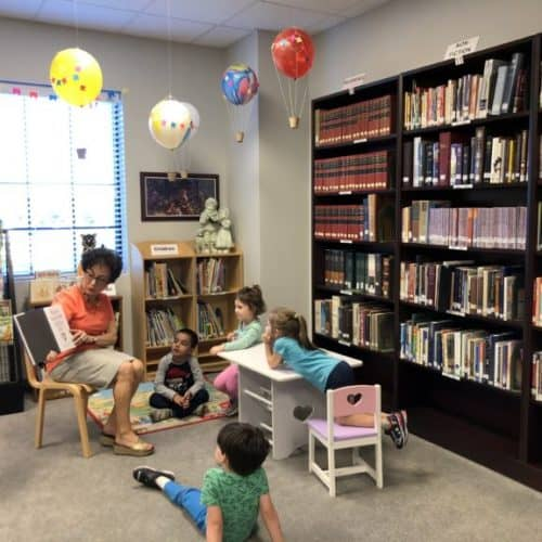 Children listening attentively to woman reading a children's book in the children's corner of the library. Hot air balloon decorations are hanging from the ceiling.