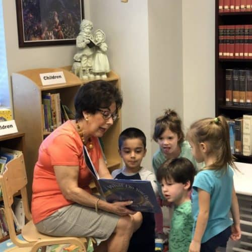 Woman reading to small children in the children's section of the library