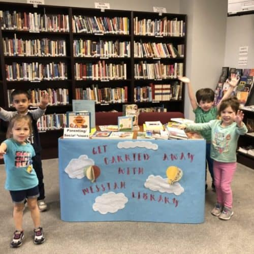 "Messiah Lutheran Library table display on Parenting/Social Issues, with four small children around the table. Table poster reads ""Get Carried Away with Messiah Library"" and depectis hot air balloons and clouds in blue sky."