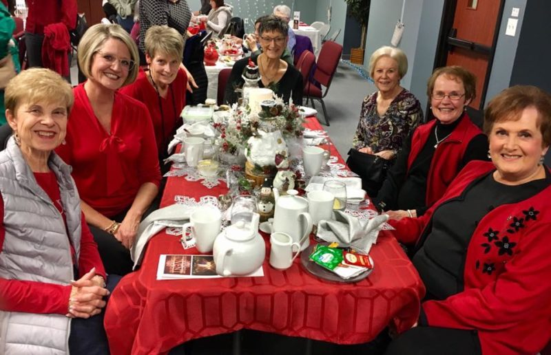 Group of women mostly dressed in red sitting at a table for holiday tea.